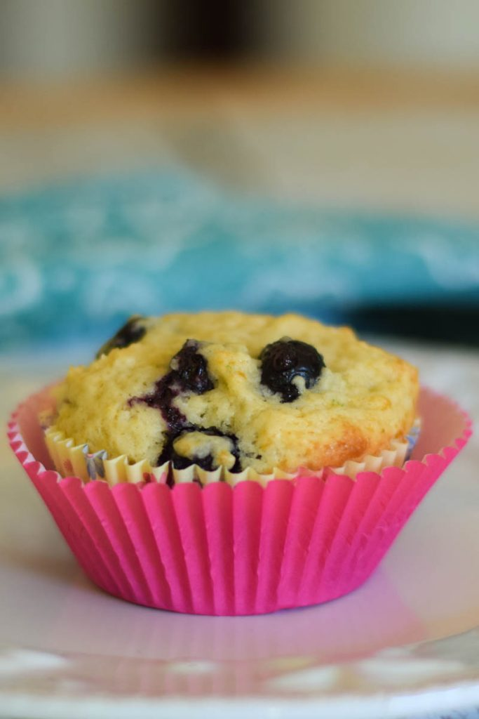 a single muffin with pink muffin wrapper and blue napkin in the background