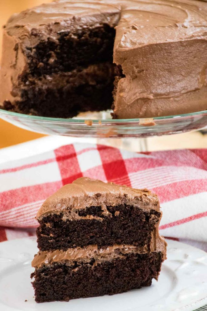 A piece of Chocolate Mayonnaise Cake on a white plate with the whole cake in the background