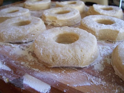 doughnuts on cutting board resting prior to deep frying