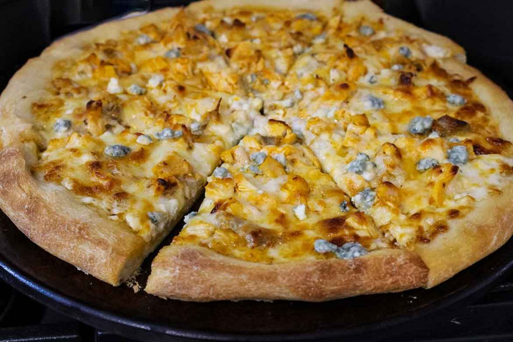 Buffalo Chicken Pizza Recipe on a pizza stone and cut into slices