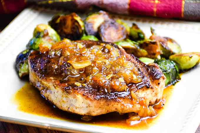 Pork with Ginger Maple Sauce on a plate with brussels sprouts in the back