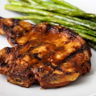 Up close image of grilled pork chop with chipotle sauce on a white plate with side of asparagus