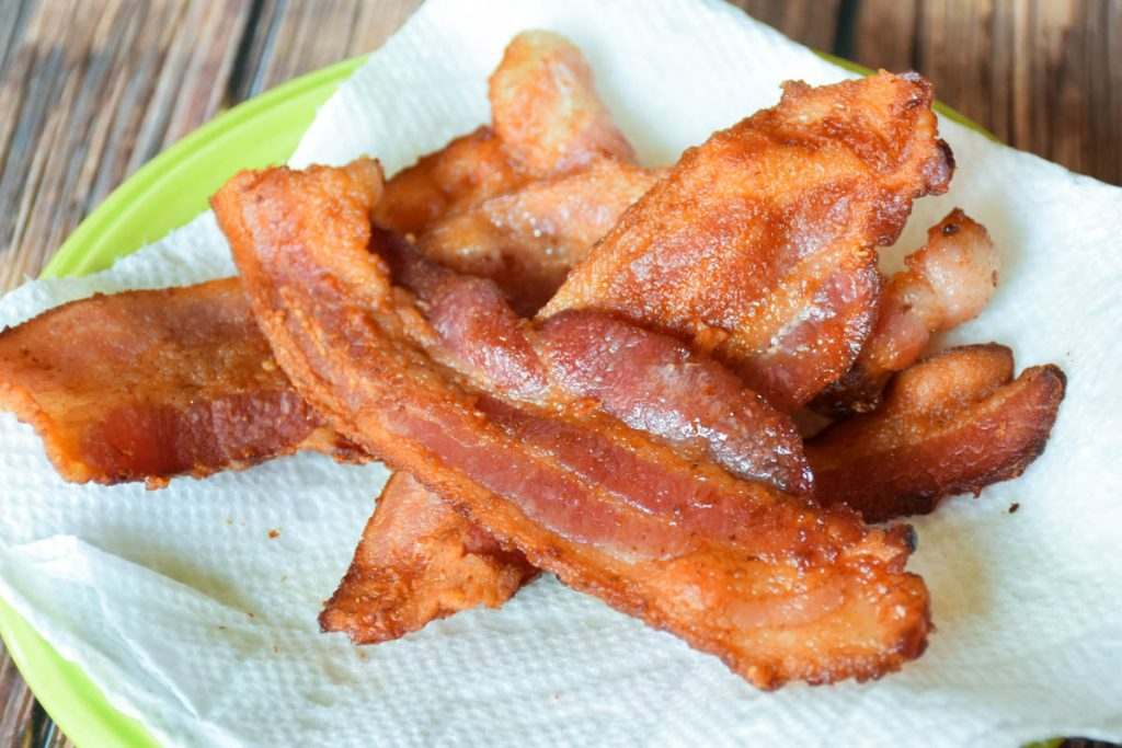 Crispy fried bacon on a paper towel lined plate