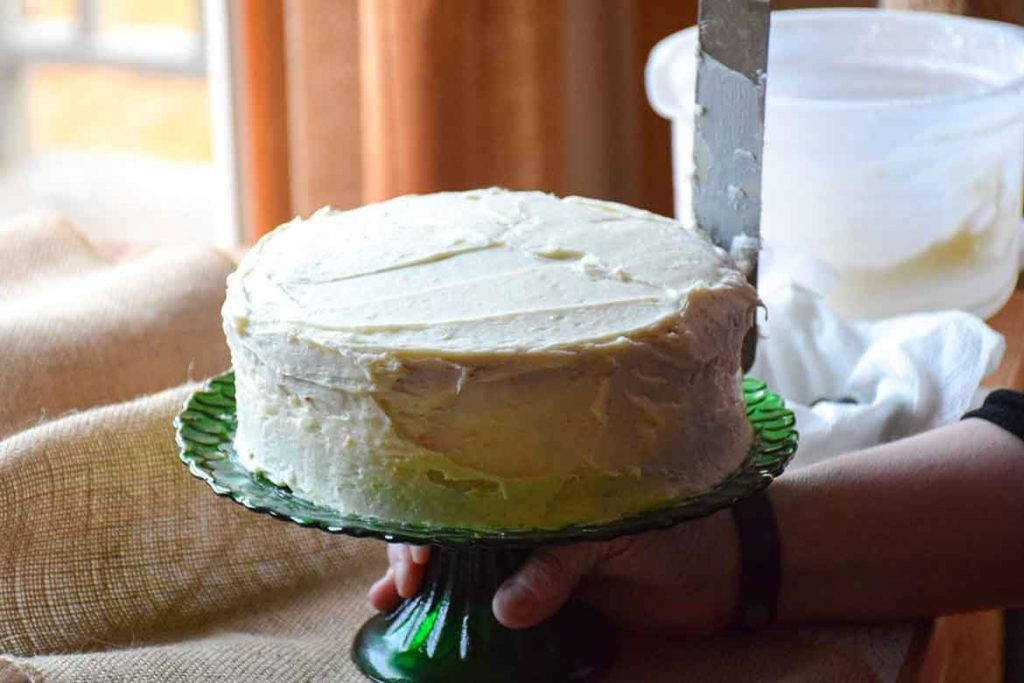 Whole cake with crumb coating of lemon cream cheese frosting