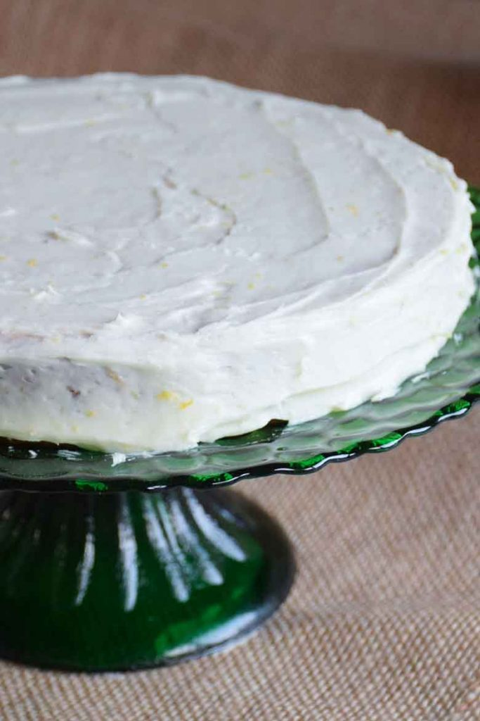 first layer of cake with lemon cream cheese frosting on a green pedestal cake plate
