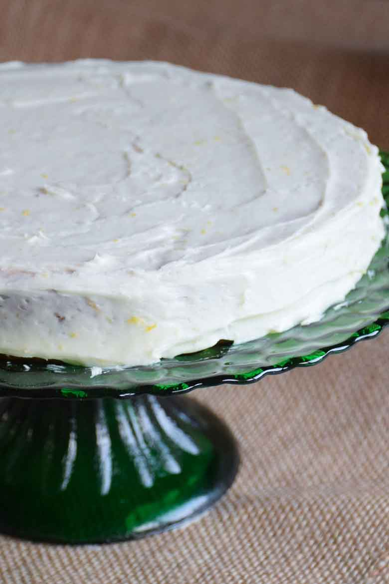 first layer of cake with frosting on a green pedestal cake plate