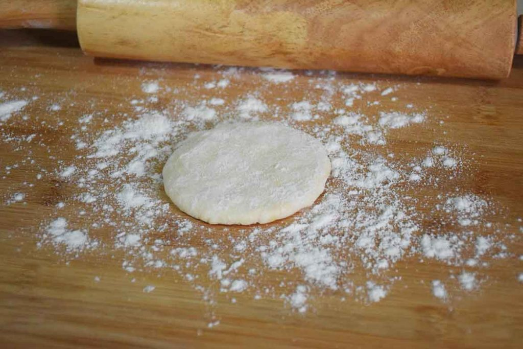 beginning to shape the dough into a tortilla on a floured board with a rolling pin