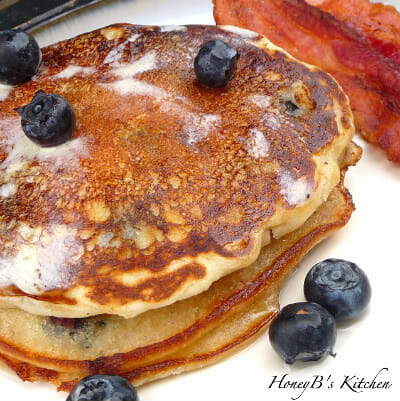 A stack of 3 pancakes on a white plate with blueberries and bacon.