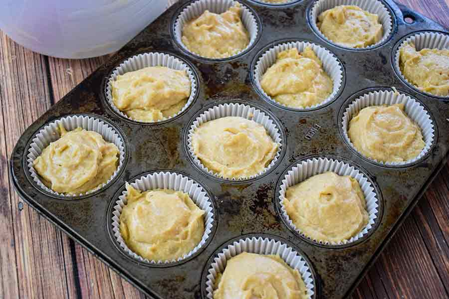 muffin batter in a muffin pan with paper liners