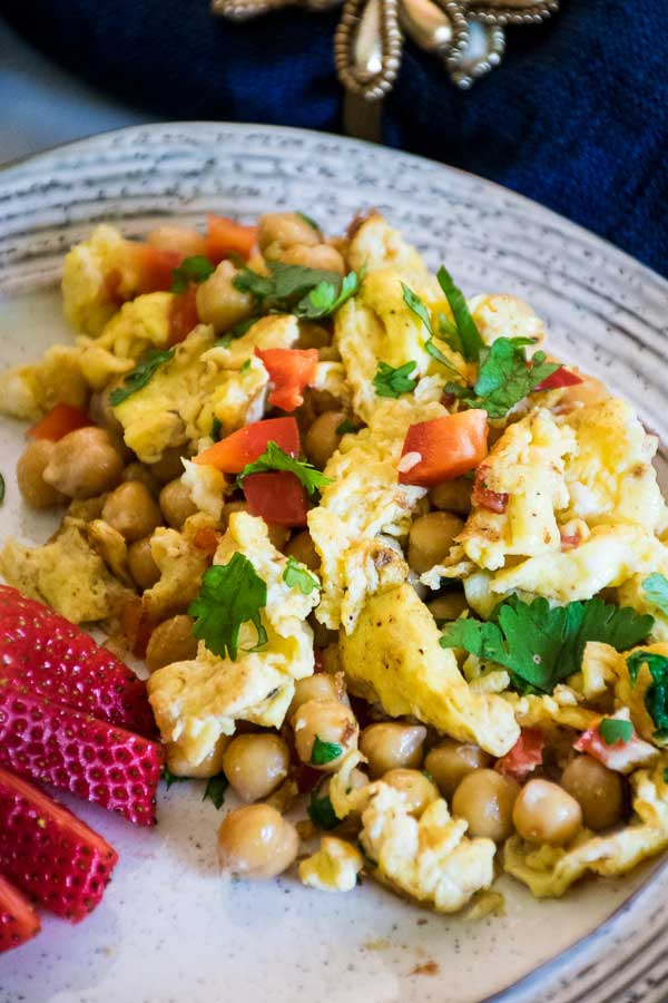 Overhead view of garlic scrambled eggs with chickpeas and cilantro with a large fresh strawberry to the left of the plate