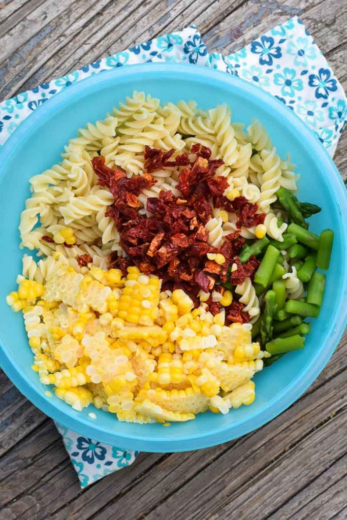Rotini, corn, sun-dried tomatoes, and asparagus in mixing bowl