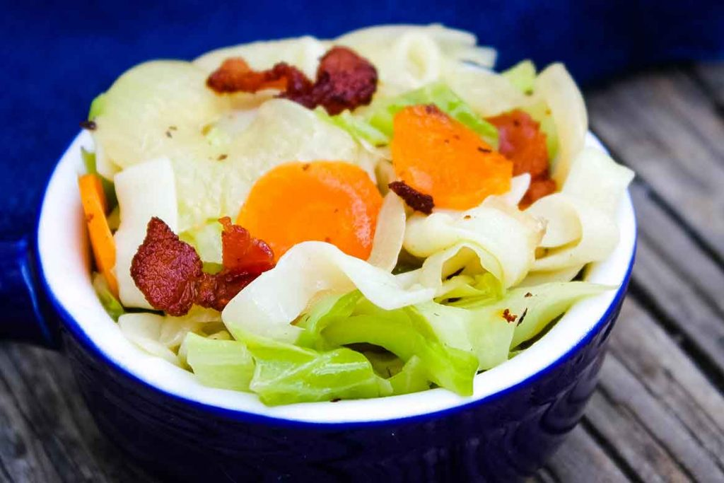 Cabbage Noodles topped with Bacon in a blue serving dish