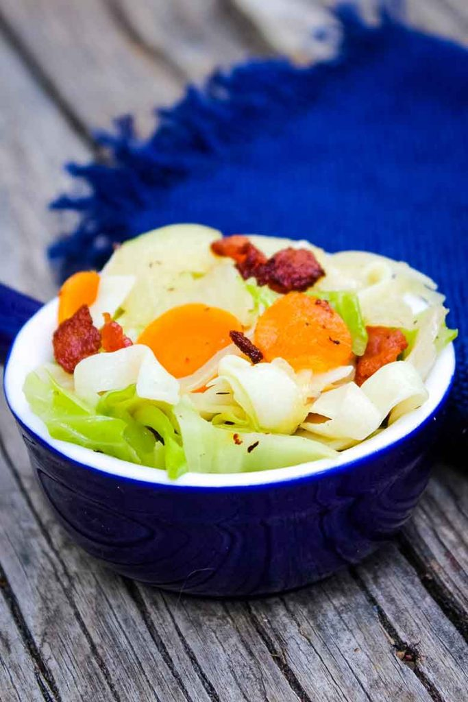Cabbage Noodles with Bacon in a blue serving bowl with a blue napkin in the background
