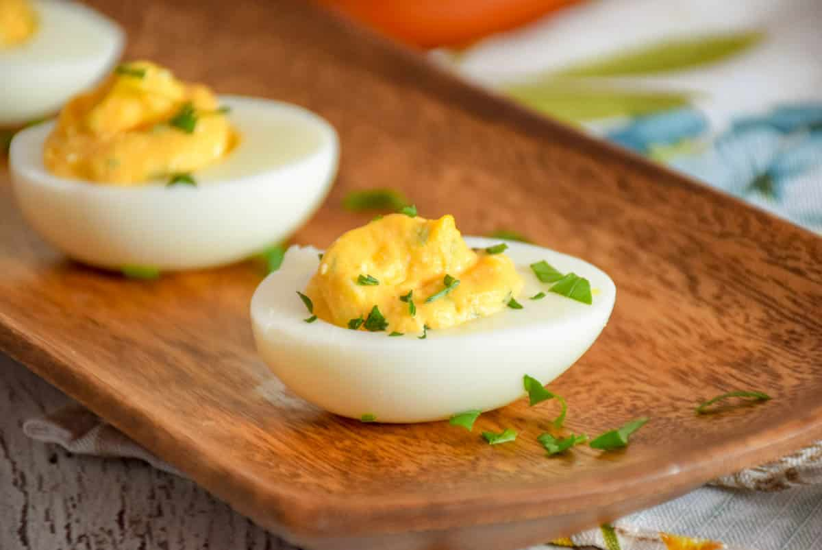 Buffalo Style Stuffed Eggs on brown acia serving tray with parsley garnish