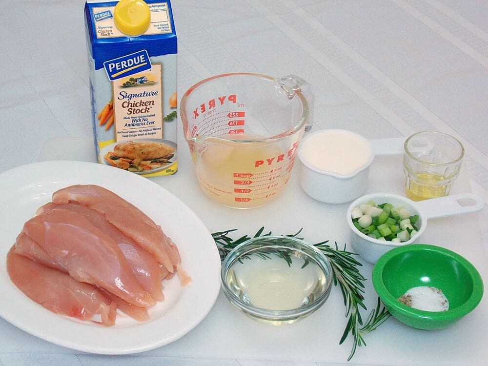raw chicken tenders on a white plate with ingredients for recipe