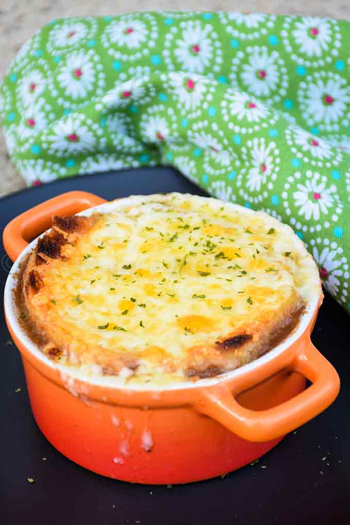 French Onion Soup in an orange soup crock with broiled cheese
