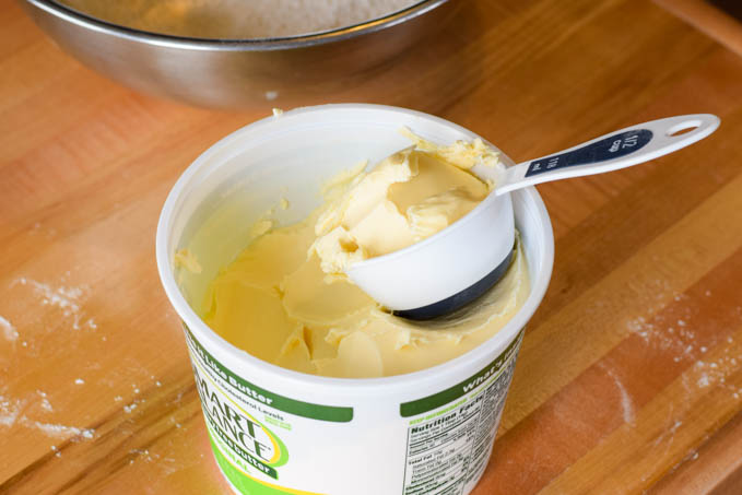 A tub of smart balance margarine open with a measuring cup filled with margarine