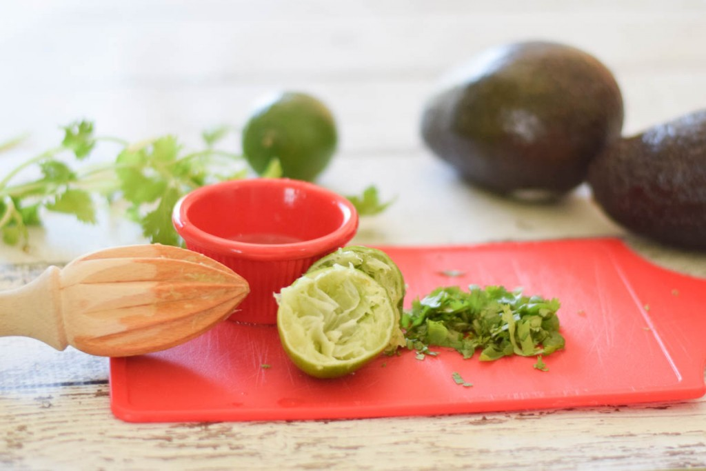 lime and cilantro on a red cutting board
