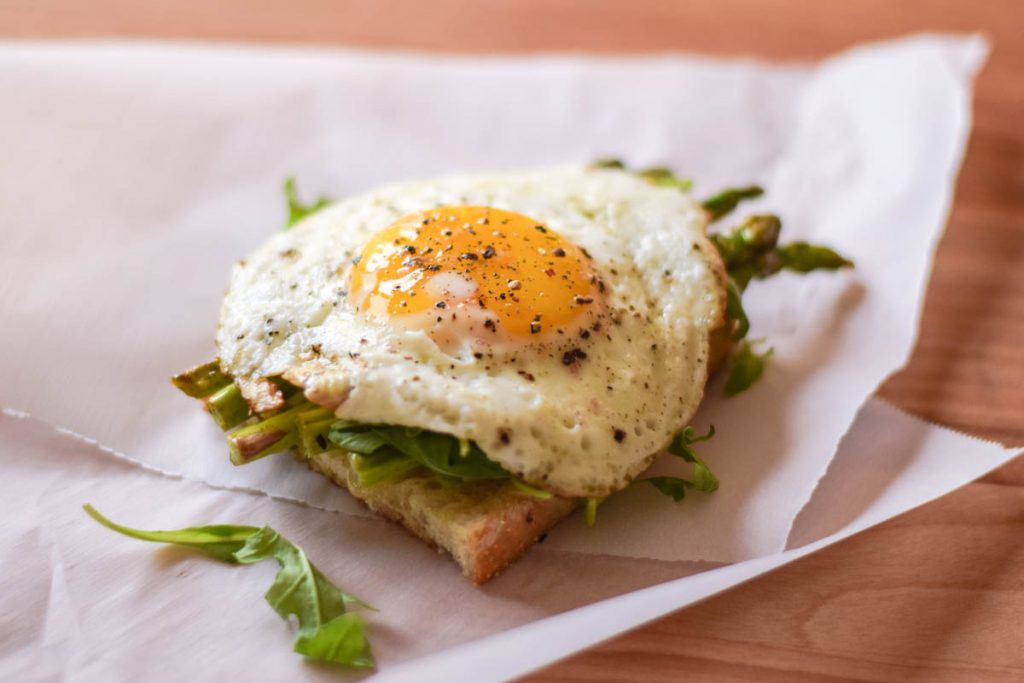 bottom layer of sandwich with cheese, asparagus, and fried egg on top