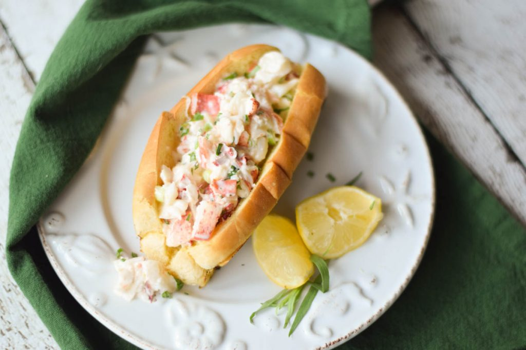 Overhead view of Classic Lobster Rolls on a seashell plate with lemon wedges and a green napkin