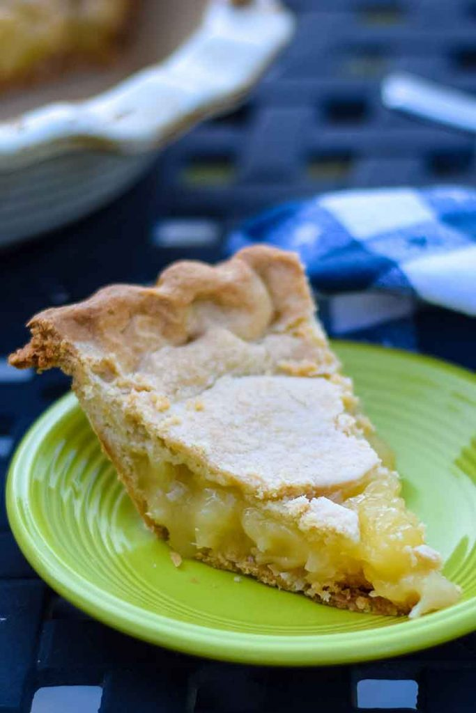 A slice of Pineapple Pie on a green plate sitting on a picnic table with a blue and white towel.