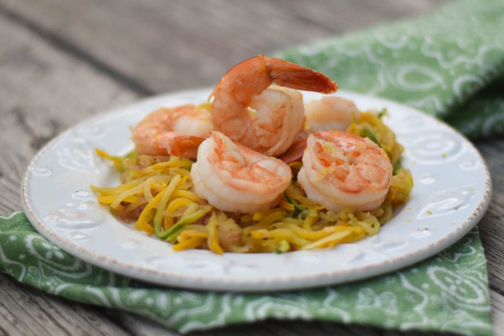 Squash noodles on a serving plate with shrimp arranged on top