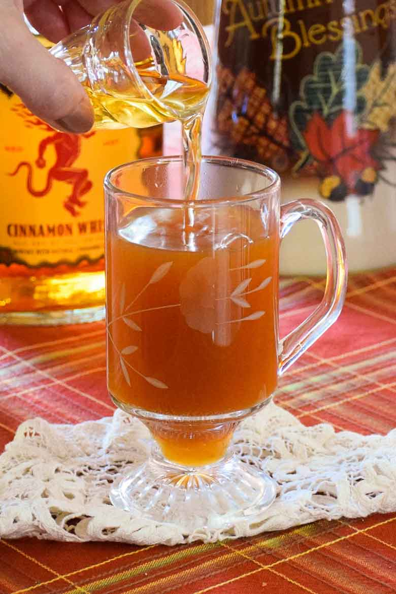 Pouring a shot glass of fireball whisky into a hot mug of apple cider