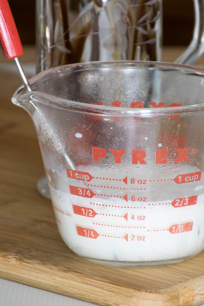 measuring cup with frothed milk