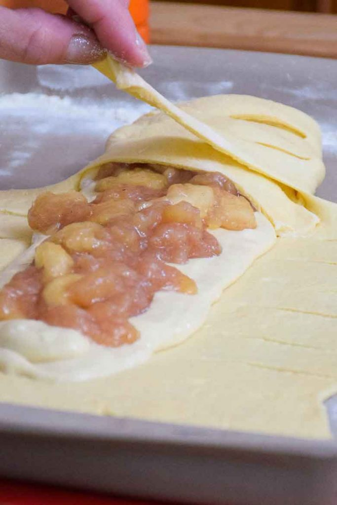 making the danish braid by wrapping the dough strips around the filling