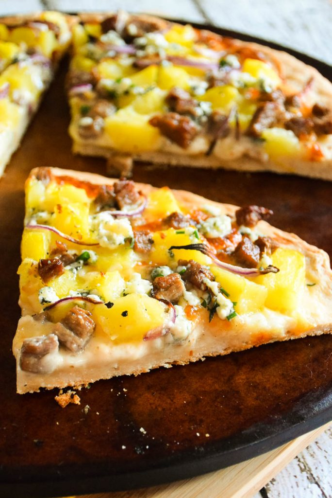 Steak and Potato Pizza sliced and on pizza stone