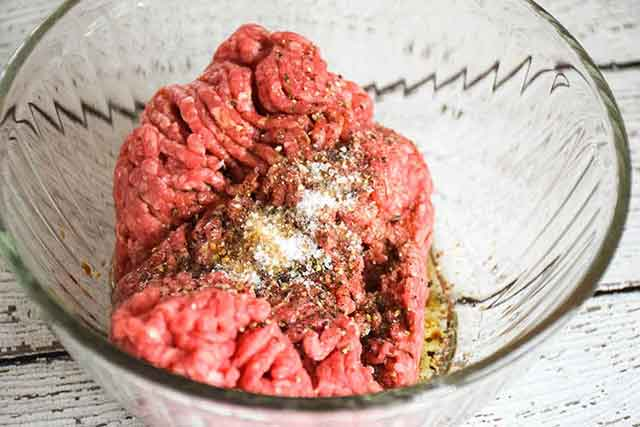 ground beef in mixing bowl with seasonings on top