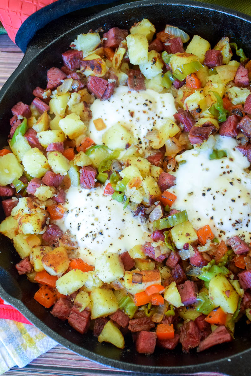 Homemade Corned Beef Hash and  Eggs in cast iron skillet, overhead shot