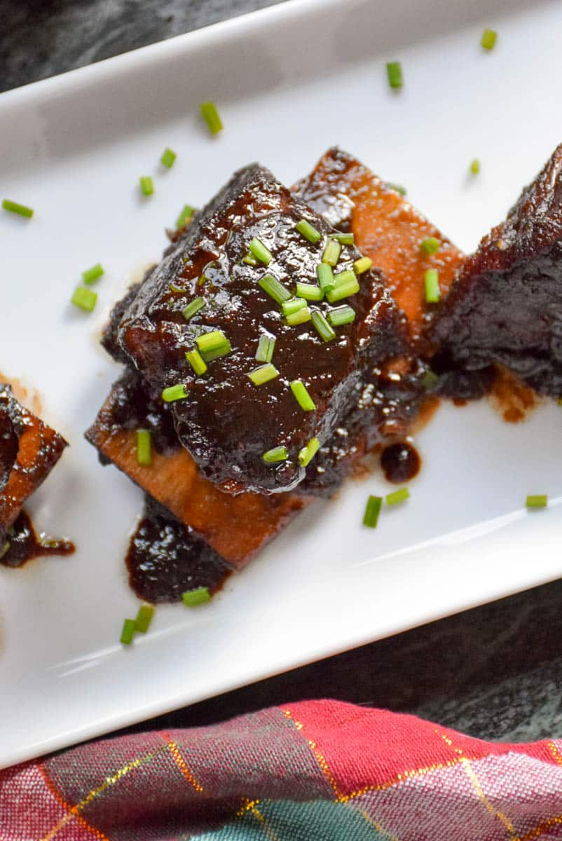 Overhead view of braised short rib appetizers on a serving tray sprinkled with chives