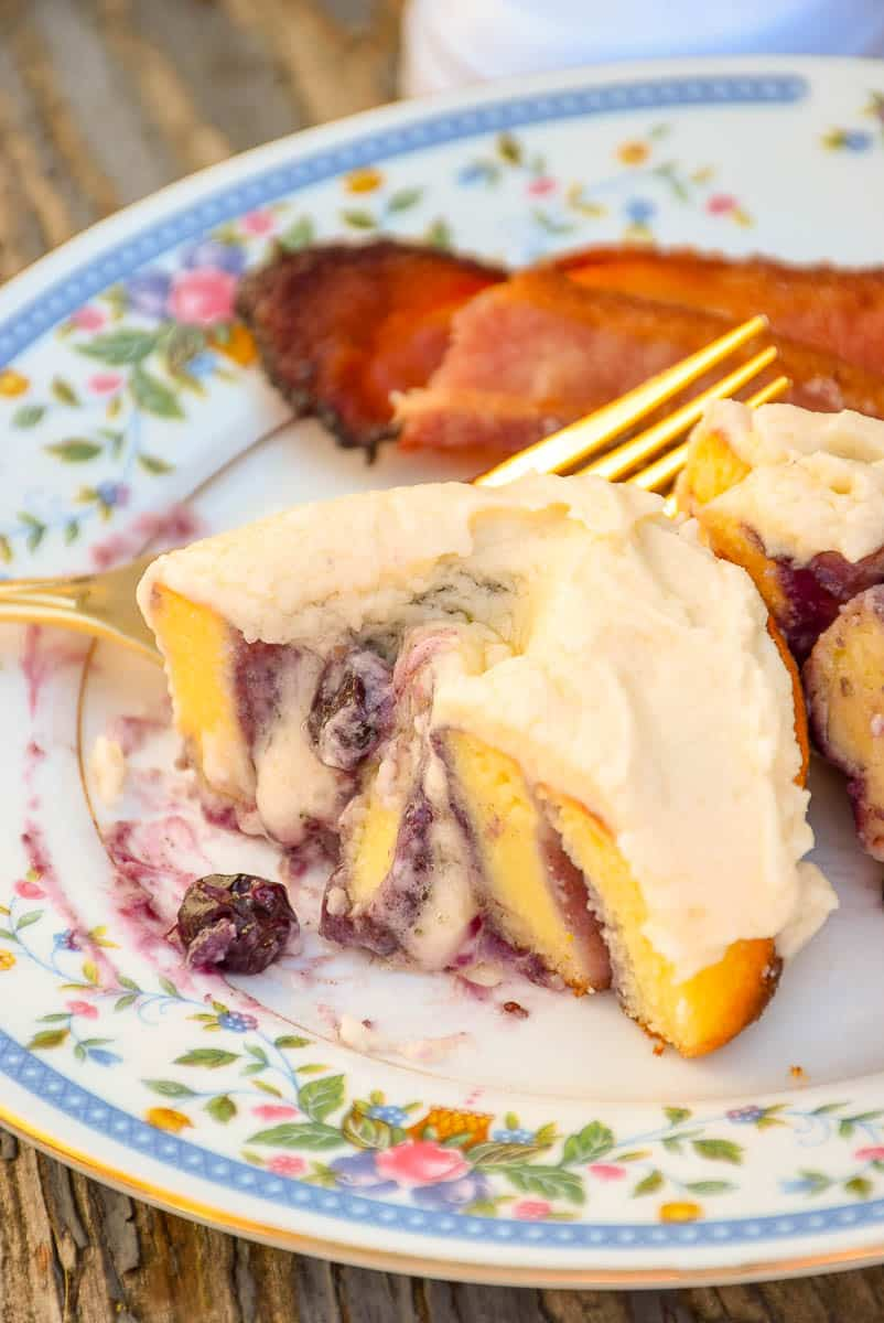 a serving of Keto Blueberry Sweet Rolls on a flowered plate with a side of bacon
