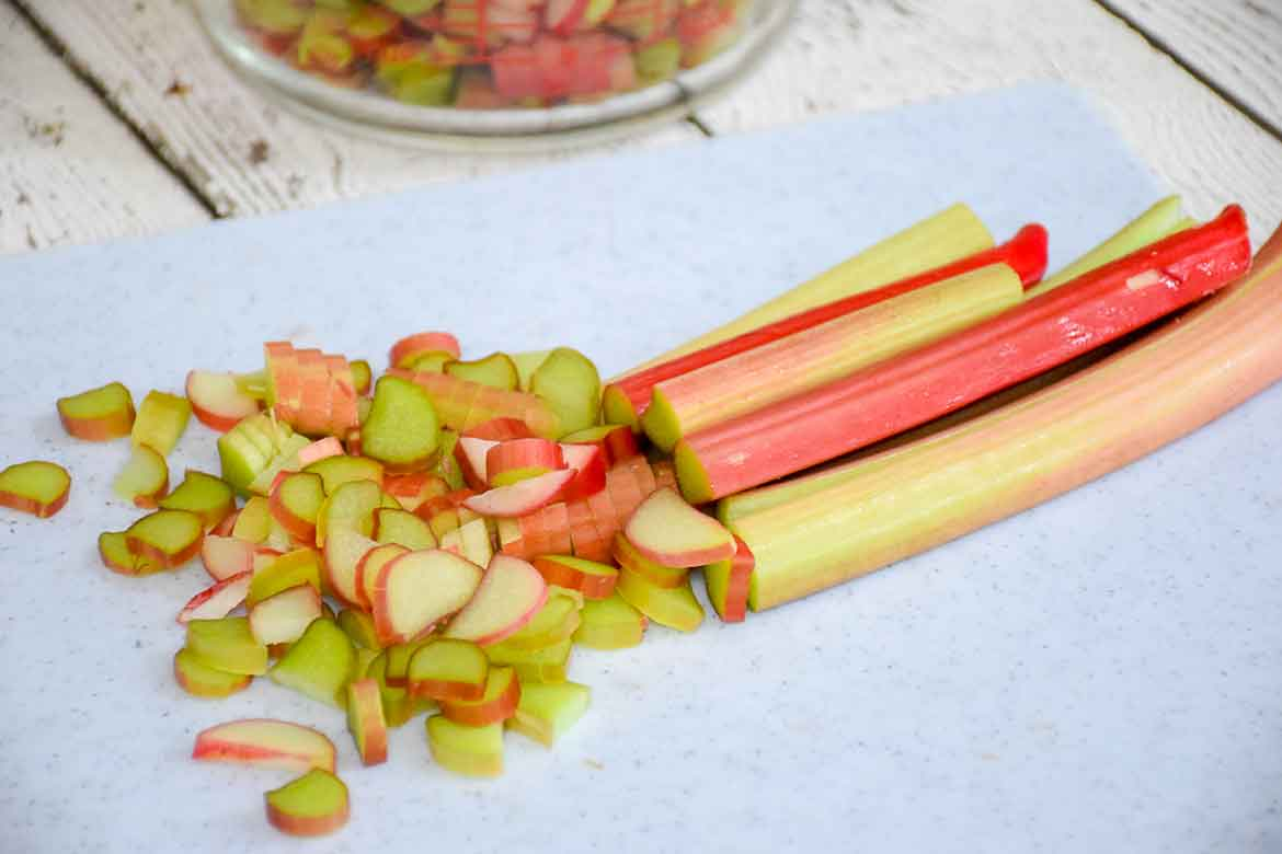 washed rubarb stalks on a cutting board with part of the stalks sliced