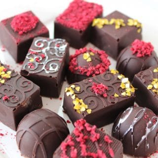 These low carb chocolate truffles will rock your partner's keto world! Smooth sugar free chocolate coats a creamy chocolate raspberry ganache filling--all topped with vibrant raspberries! #ketotruffles #chocolatetruffles #ketochocolateraspberrytruffles #ketocandy