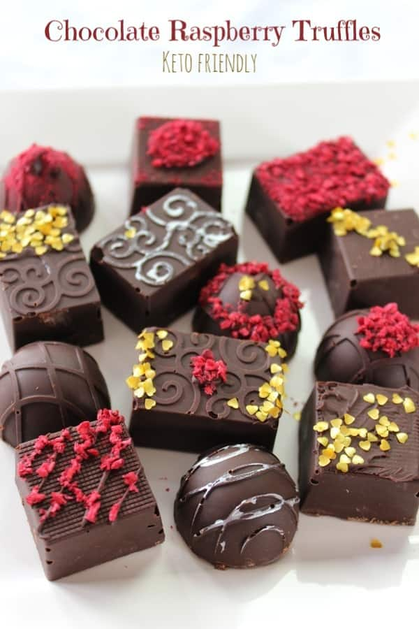These low carb chocolate truffles will rock your partner's keto world!  Smooth sugar free chocolate coats a creamy chocolate raspberry ganache filling--all topped with vibrant raspberries! #ketotruffles #chocolatetruffles #ketochocolateraspberrytruffles #ketocandy #lowcarbtruffles #sugarfreecandy