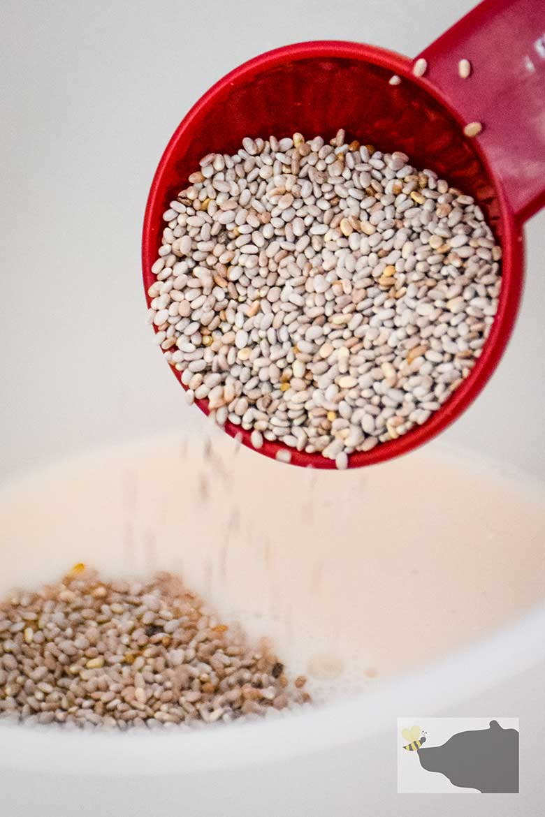 Chia seed in tablespoon being poured into liquid