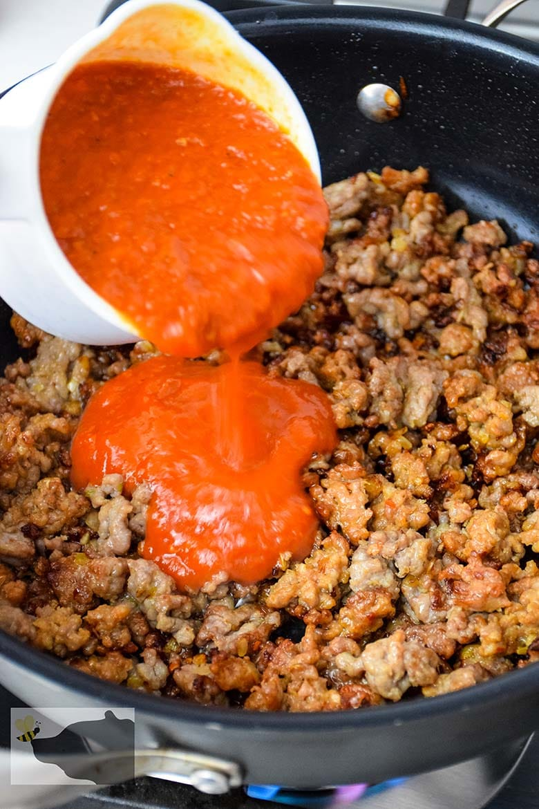pouring the marinara over top of the cooked ground sausage mixture in the skillet