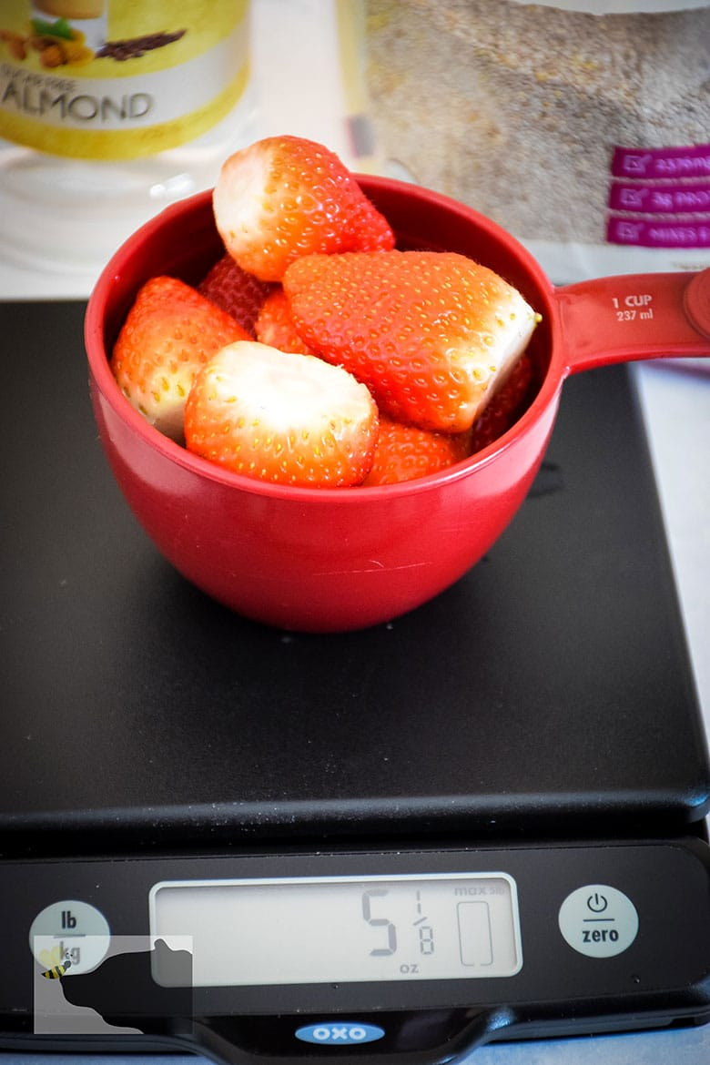 Whole Strawberries in 1 cup measure on XOX scale showing weight of 5.5 ounces
