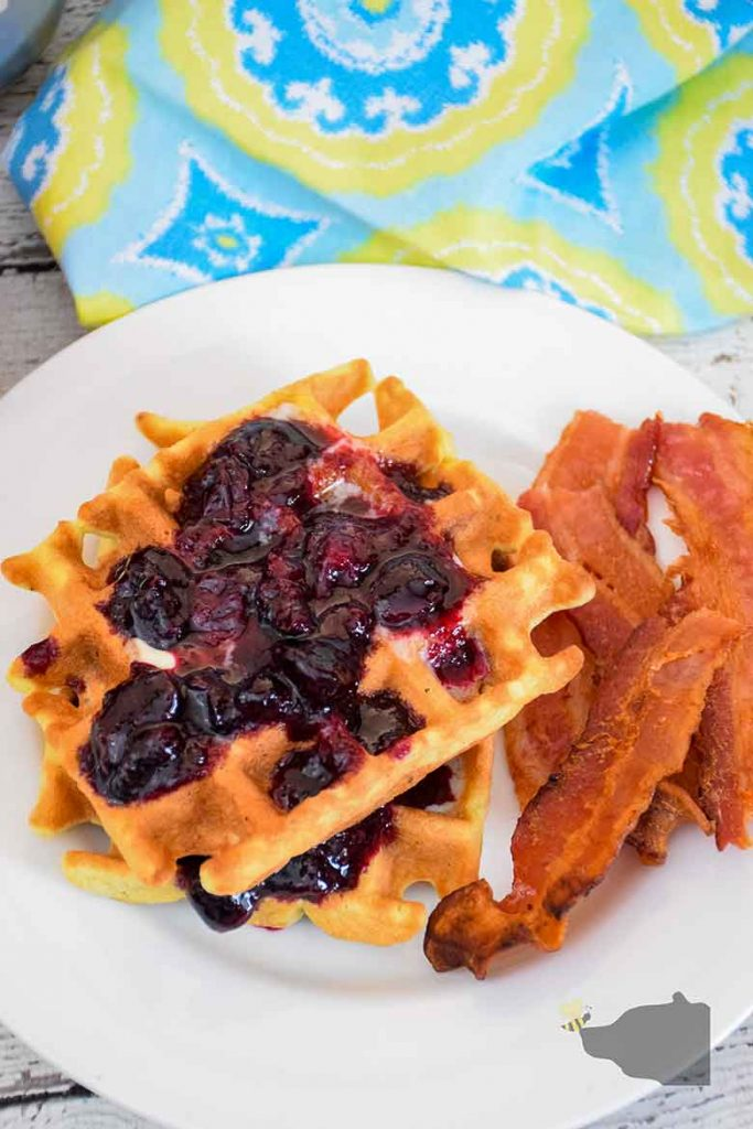Overhead shot of two blueberry waffles with blueberry sauce and bacon on a white plate