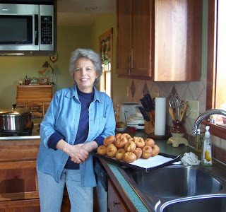 Mom standing in her kitchen with a tray of homemade buttermilk doughnuts on the counter beside her.