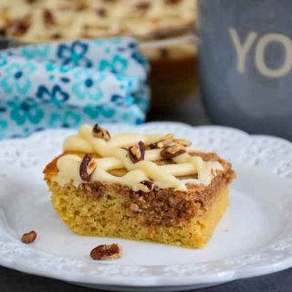 A slice of pecan coffee cake with cinnamon swirl on a white plate with blue and white flowered napkin with baking dish in back and gray coffee mug to the right