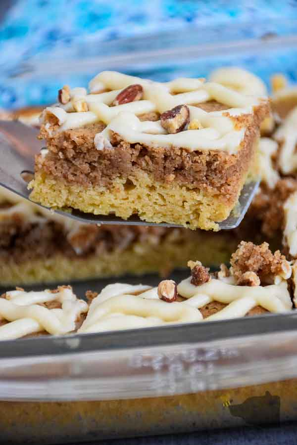 removing a slice of pecan coffee cake from baking dish to serve