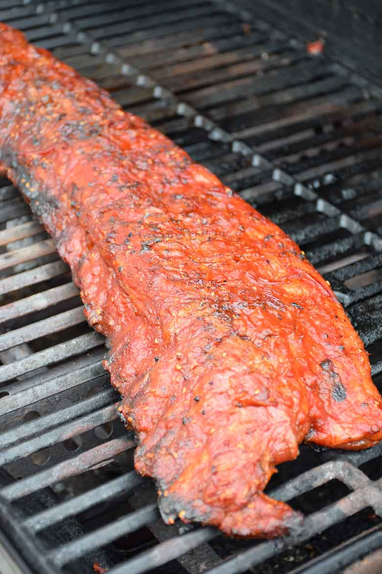 cooked pork back ribs with Raspberry Chipotle Sauce on the grill ready to plate