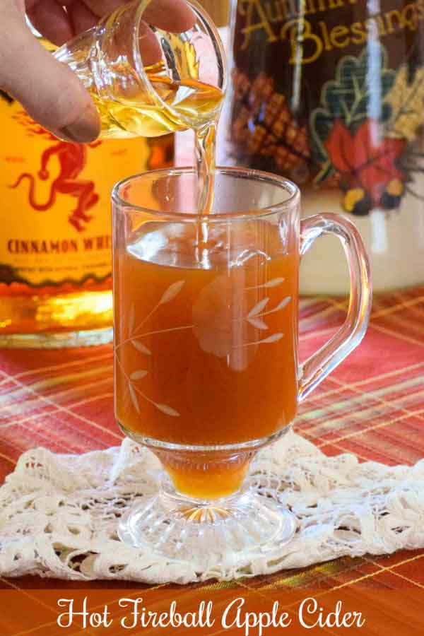 Pouring a shot of cinnamon flavored whiskey into a hot mug of apple cider