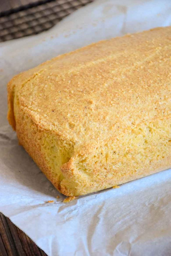 A grain free Baked loaf of Keto Bread before cutting into slices sitting on parchment paper