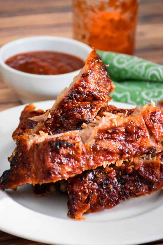 Pork Back Ribs on a plate with a small side of sugar-free Raspberry Chipotle Barbecue Sauce