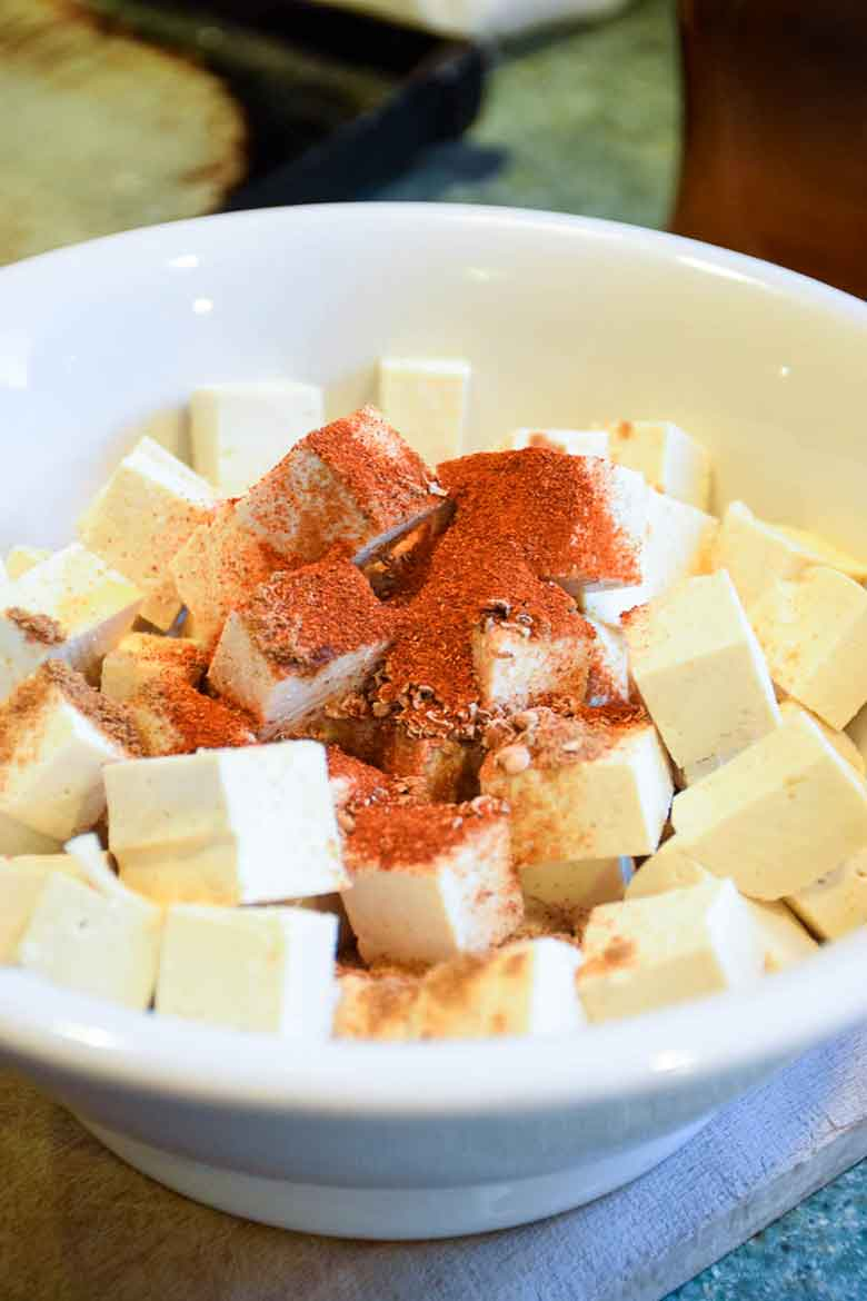 Tofu cubes in mixing bowl with spices sprinkled on top prior to tossing to coat pieces