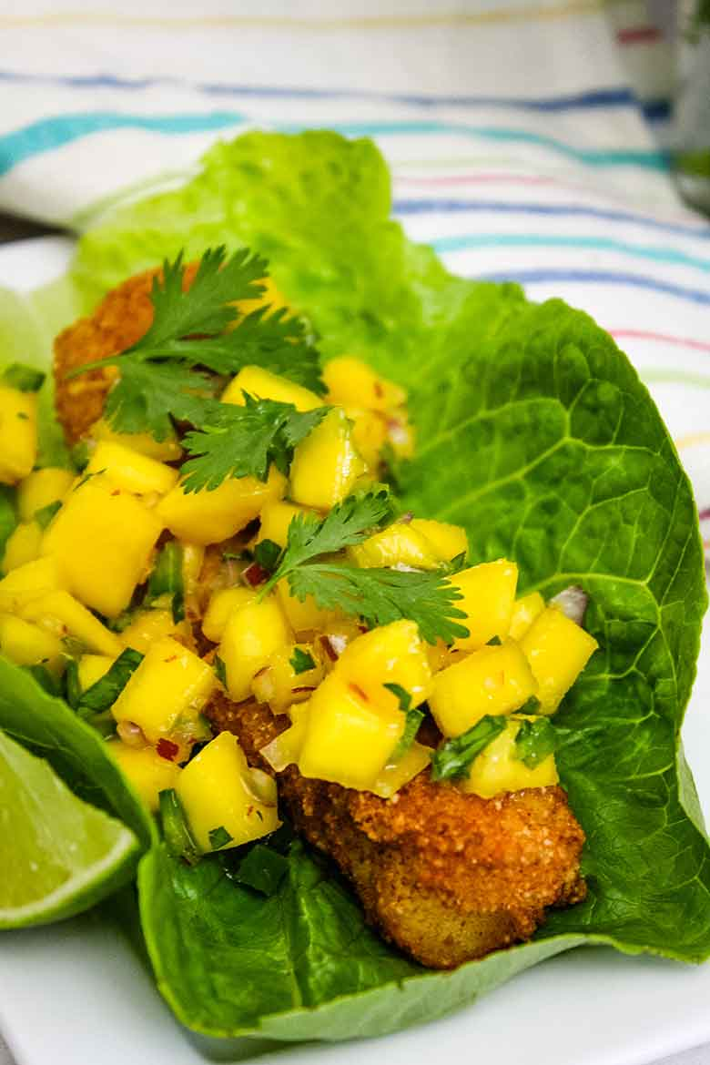 A Cod Fish Taco topped with Spicy Mango Salsa in a lettuce cup.